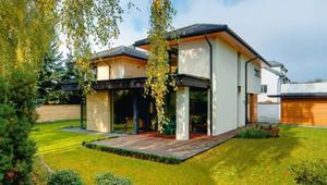 Nowoczesny dom jednorodzinny z dużymi oknami i drewnianymi tarasami. ZDJĘCIA